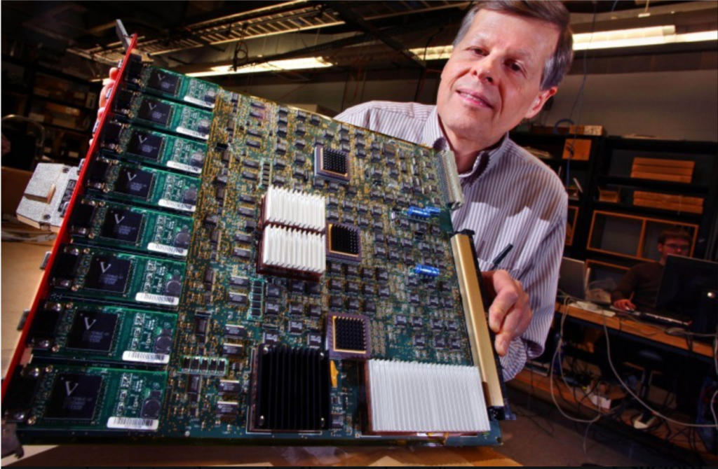 Wesley Smith holds a large electronics board full of circuits and wires