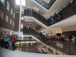 women from many Midwest schools stand behind their schools' banners on a stair case where the conference was held