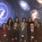 group photo in front of an astronomy and galaxy-themed backdrop