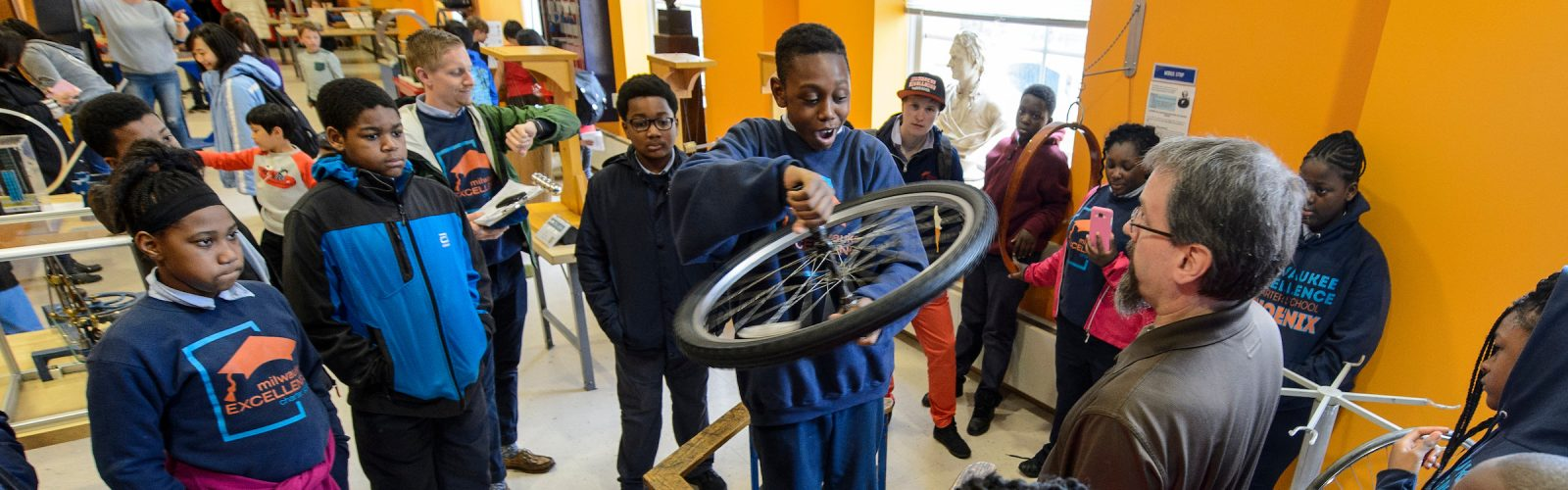 several young students watch in the physics museum as one student holds a spinning bike wheel while standing on a rotatable platform