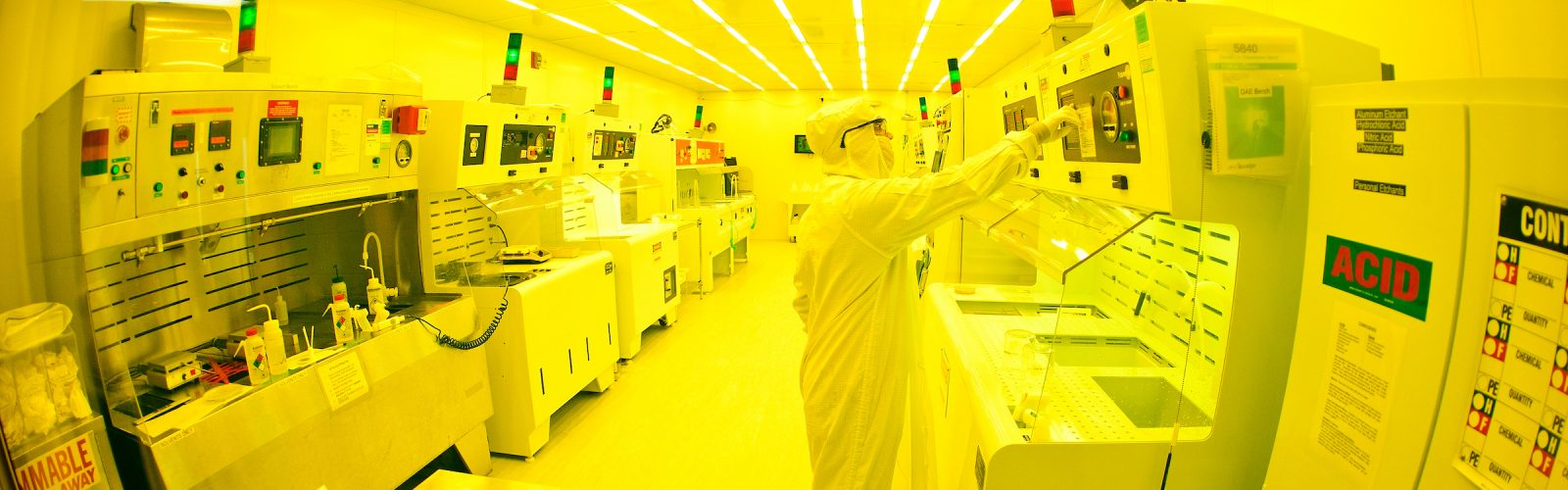a very yellow-hued image of a person in a full-body clean suit working in a clean room