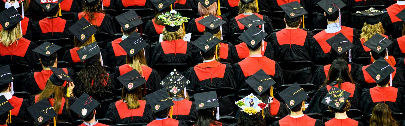 rows of graduates in regalia, sitting in chairs