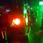 the apparatus hosting the rare earth metal doped crystal glows orange, and the background of the photo has a green fluorescence hue from the input laser