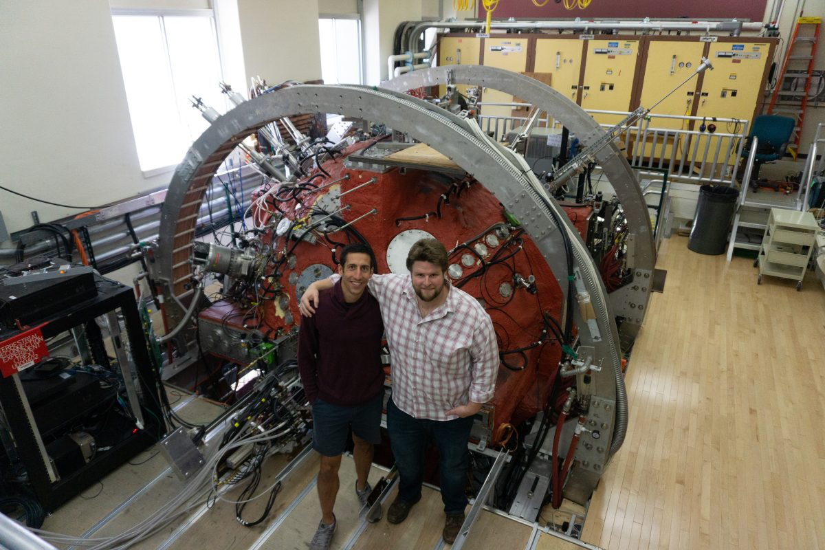 two graduate students stand in front of the Big Red Ball, a large spherical instrument painted red