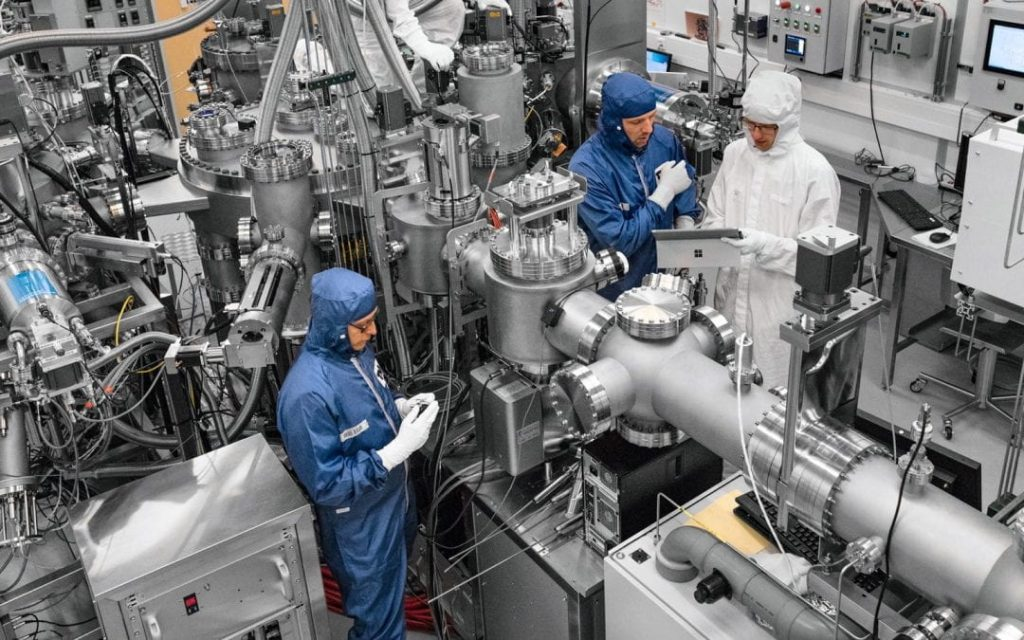 people in blue clean suits in a computer / electronics room