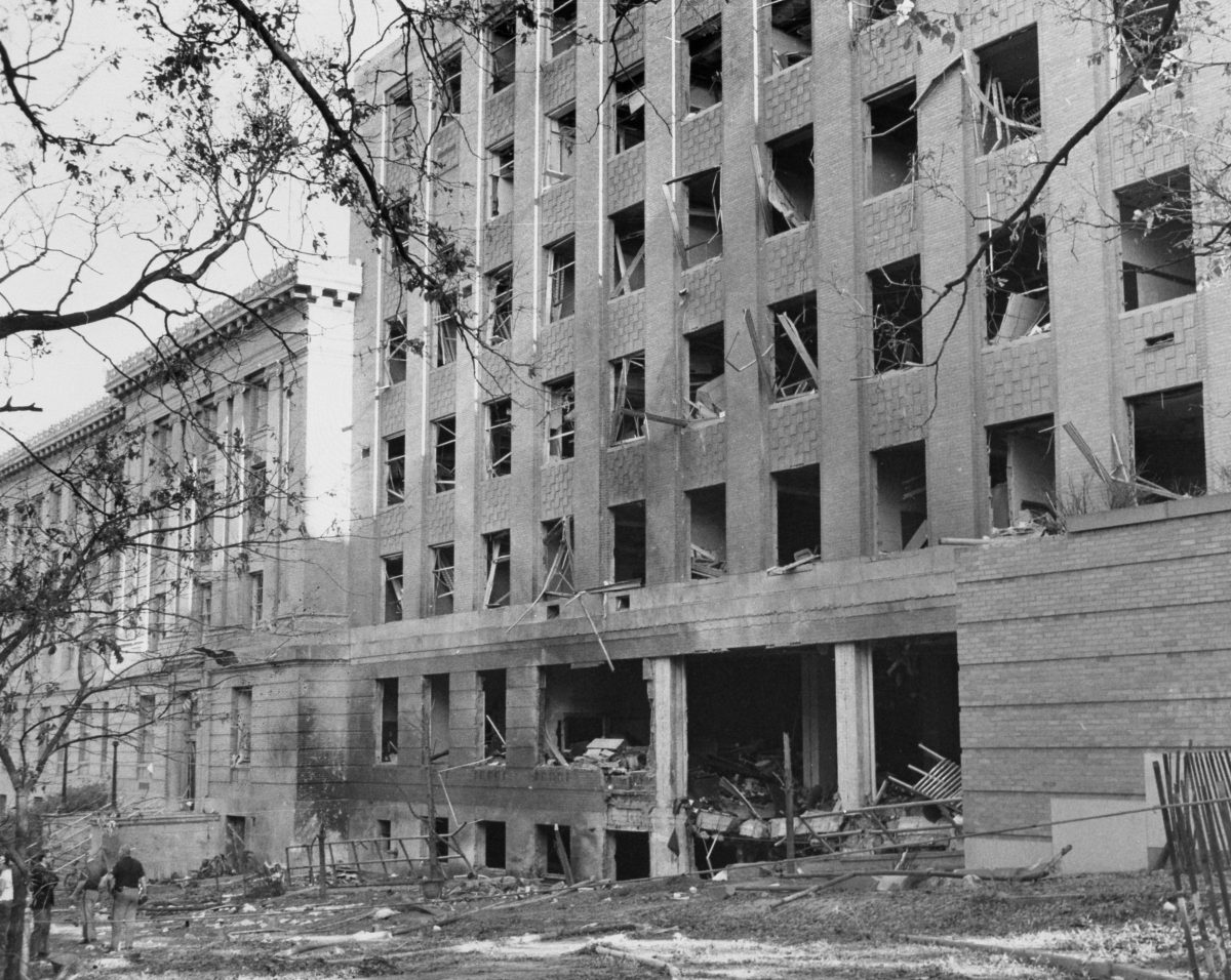 black and white photo of Sterling Hall after the bombing shows a building with windows blown out and obvious damage.