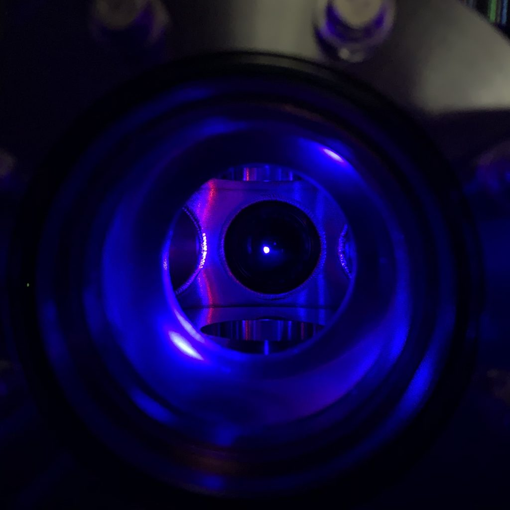 a blue-laser-hued image of a trapped ball of strontium ions in an optical lattice clock