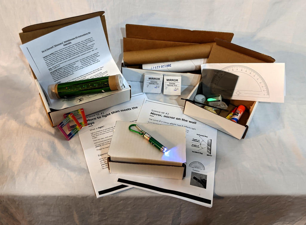 the 4 kits sent home with the students are laid out and opened up, revealing contents like worksheets, laser pointers, mirrors, and lenses