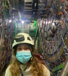 a woman in a helmet wearing a disposable facemask stands in front of lots of metal hardware and wires
