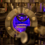 a metalilc chamber with a blue glowing orb of illuminated atoms in the center