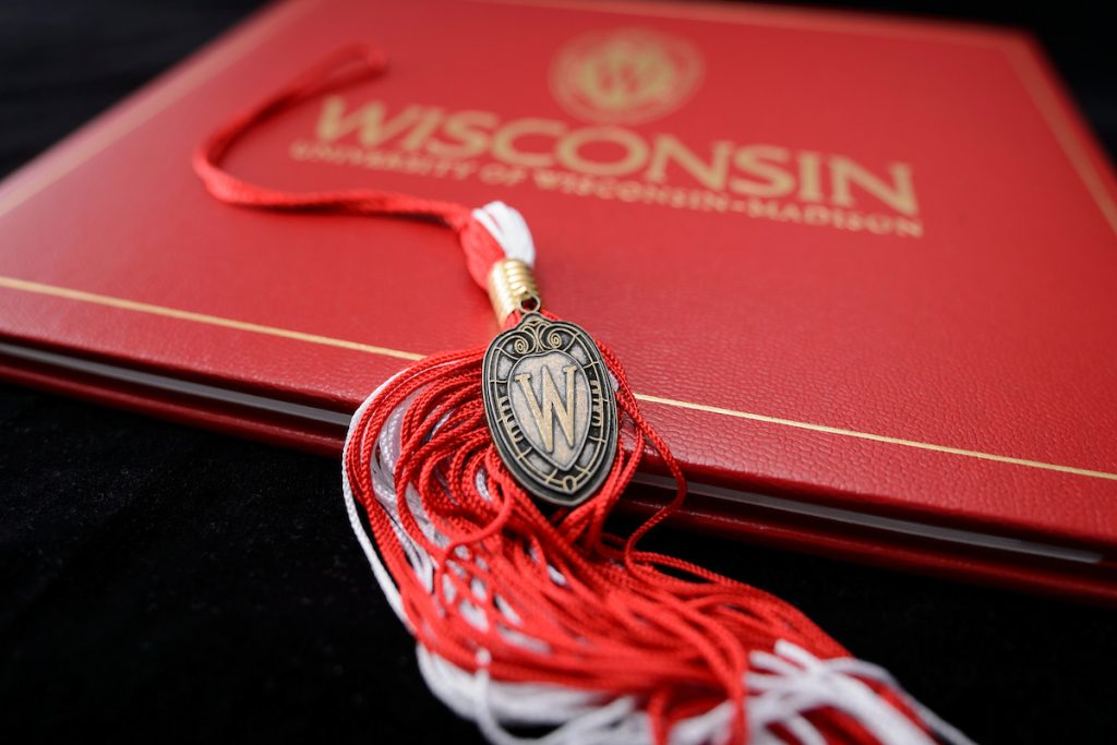 A graduation tassel with a pendant of the W crest is pictured