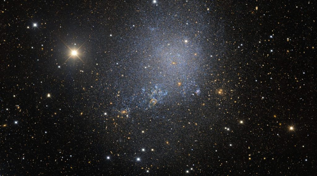 a mostly-black photo of space with white and off-white and blue dots of stars, more concentrated in the middle of the photo and representing the irregular dwarf galaxy