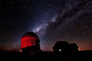 a dimly-lit domed-top observatory on the left at night, with the glow of the milky way visible in the sky above it