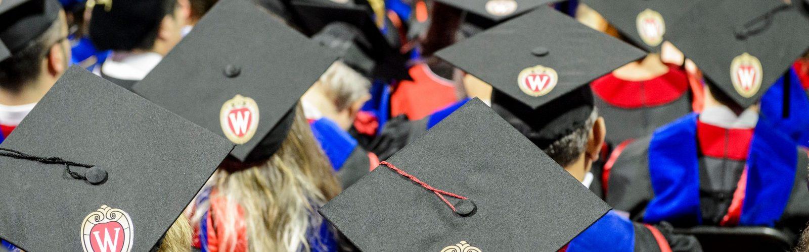 focus on graduation caps in a crowd of graduates