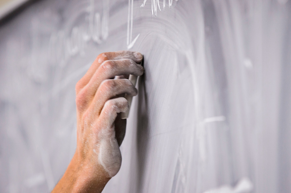 a hand writing on a chalkboard