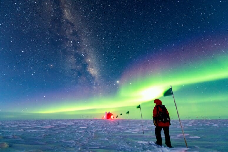 a bundled up person in the snow with the neon green glow of an aurora overhead