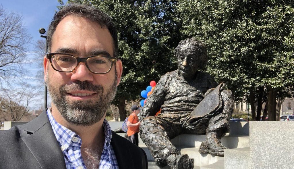 Kyle Cranmer stands next to a statue of Einstein sitting